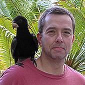 Portrait Mario Ludwig in Madagaskar - mit schwarzem Papagei auf der Schulter